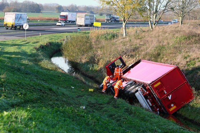 Bergers bekijken hoe ze de vrachtwagen vanuit de sloot langs het talud van de toerit A15 richting Gorinchem weer op zijn wielen kunnen krijgen.