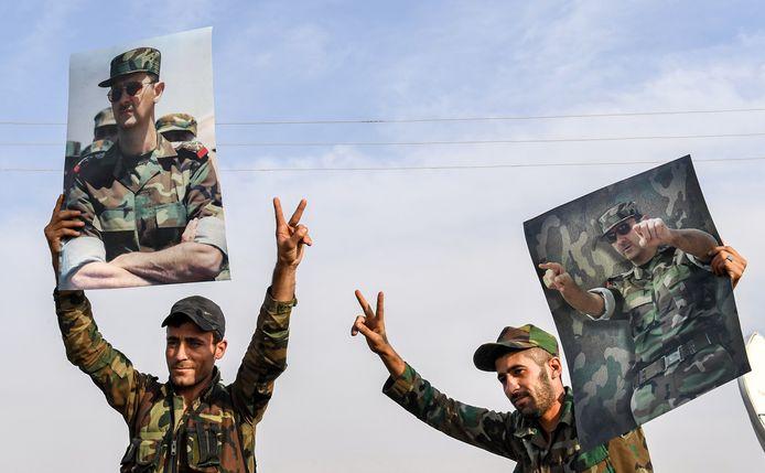 Syrische strijders houden foto's van Assad omhoog.