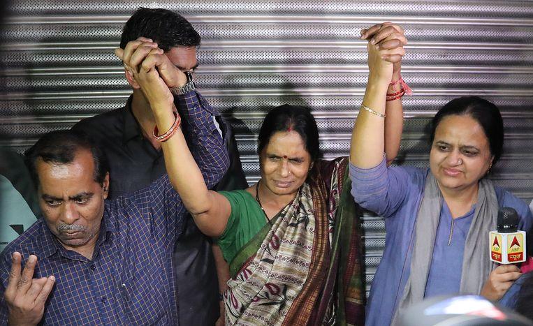 De vader (links) en moeder (midden) van het slachtoffer, na het voltrekken van het doodvonnis van de daders. Beeld EPA