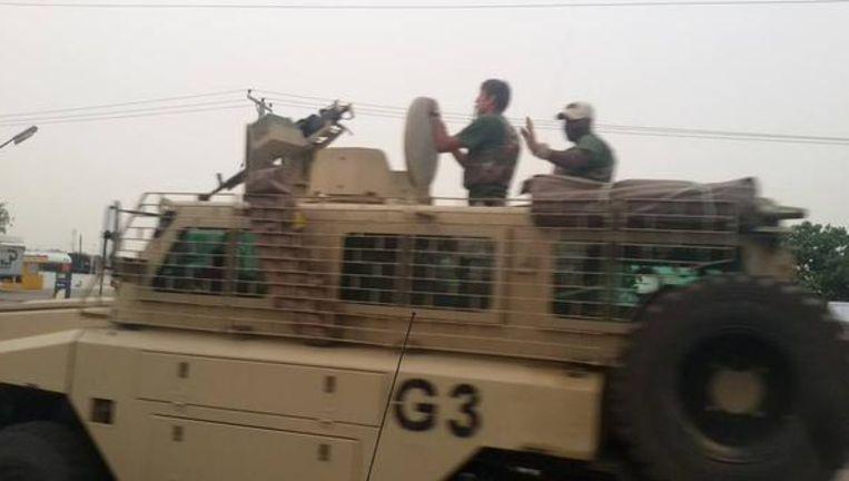 Foto van Twitter met een blanke man op een militair voertuig dat volgens persbureau Reuters door de Nigeriaanse stad Maiduguri rijdt. Beeld -