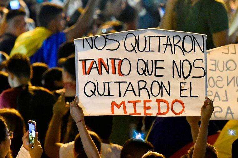 Een vrouw houdt een plakkaat omhoog waarop staat: 'Ze hebben zoveel van ons afgenomen dat ze zelfs onze angst hebben afgenomen.' Beeld AFP