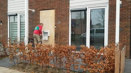 De verbrijzelde voordeur is afgewerkt met een dikke plank.  Een monteur repareert het berichtenvak op het bord.