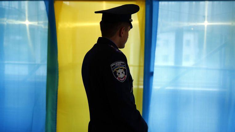 Een Oekraïnse politieagent voor enkele stemhokjes in het de provincie Ivano-Frankivsk Oblast.