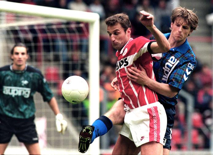 PSV'er Rene Eijkelkamp in duel met Cees Marbus van Go Ahead Eagles. Op de achtergrand kijkt keeper Oscar Moens aandachtig toe.