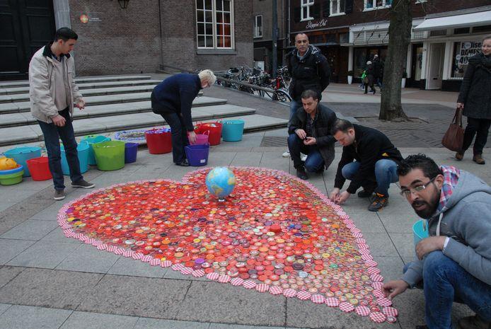Met man en macht wordt op het Kerkplein gebouwd aan een tapijt voor Vrede en Gelijkwaardigheid