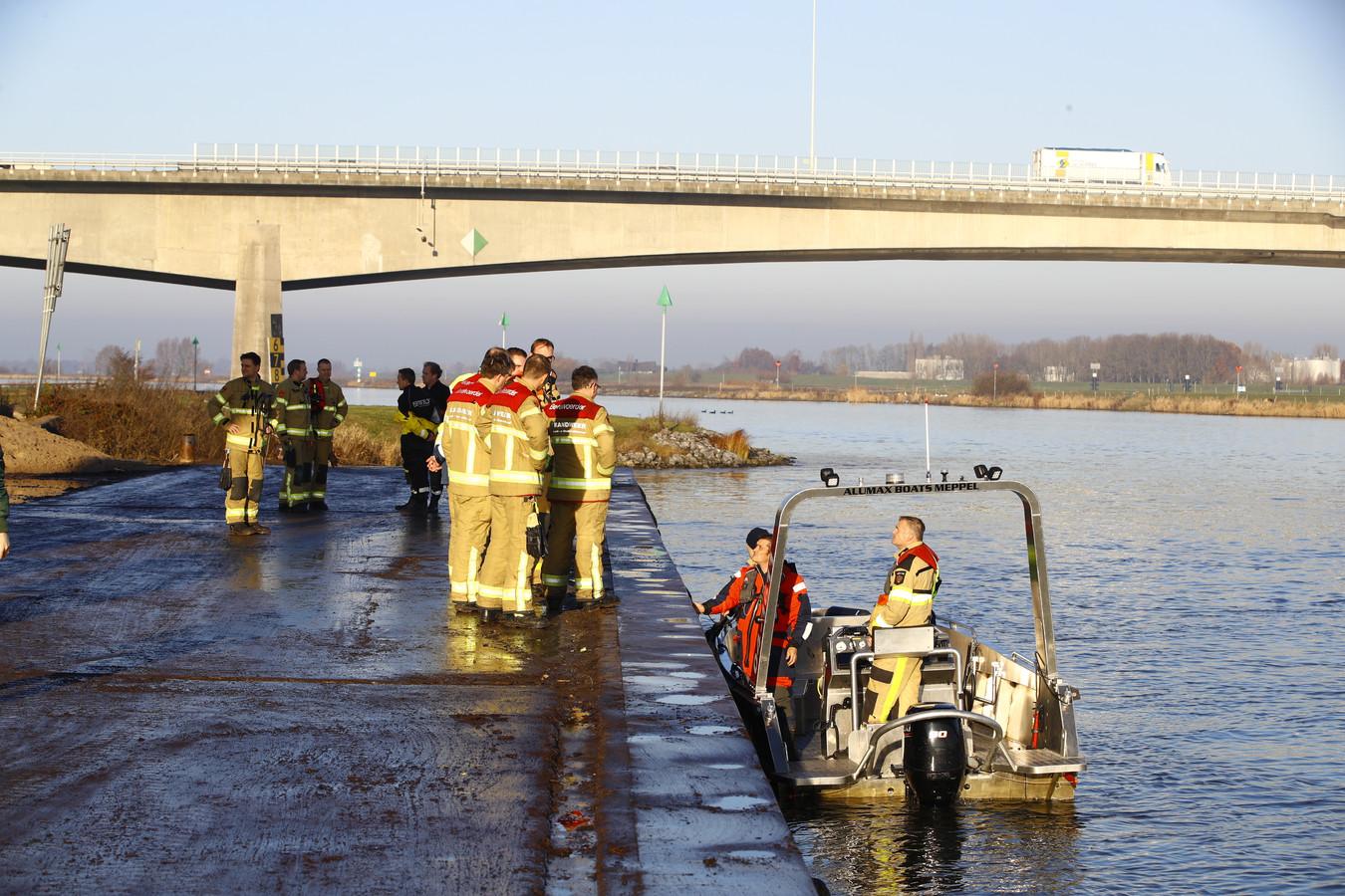 Brandweermensen steken van wal voor de zoektocht naar de mogelijke drenkeling.