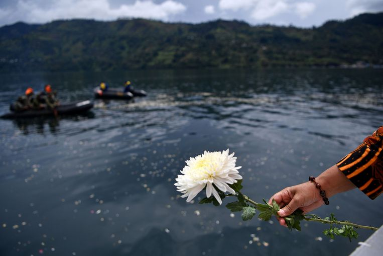 Een nabestaande gooit bloemen in het Tobameer in het noorden van Sumatra.