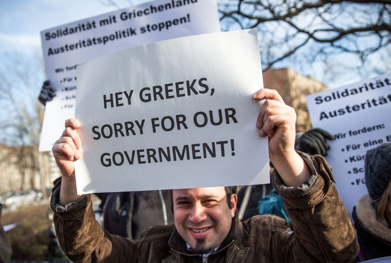 epa04604330 A protester holds a placard that reads 'Hey Greeks, sorry for our Government!' in front of the German Ministry of Finance in Berlin, Germany, 05 February 2015. The meeting between Varoufakis and Schaeuble comes after the European Central Bank (ECB) decided to turn up the pressure on Greece over its vow to renegotiate the terms of its bailout by refusing to accept Greek government bonds as security for loans.  EPA/MICHAEL KAPPELER Beeld EPA