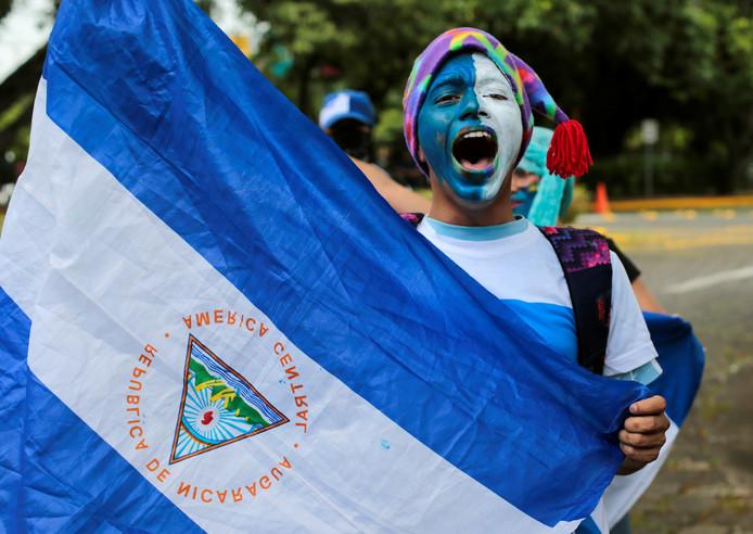 Een demonstrant in Nicaragua met de nationale vlag in handen.