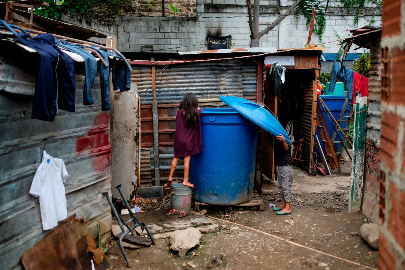 Twee kinderen zoeken naar water in de Venezolaanse hoofdstad Caracas.
