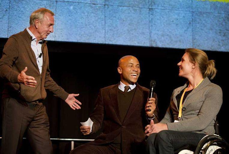 Johan Cruijff in gesprek met gastheer Umberto Tan er tennisster Esther Vergeer tijdens de tweede Cruyff Foundation Seminar. Dit jaar stond het Seminar in het teken van innovatie en ambitie in de sport en wordt gehouden in de Sporthallen Zuid in Amsterdam. Beeld anp