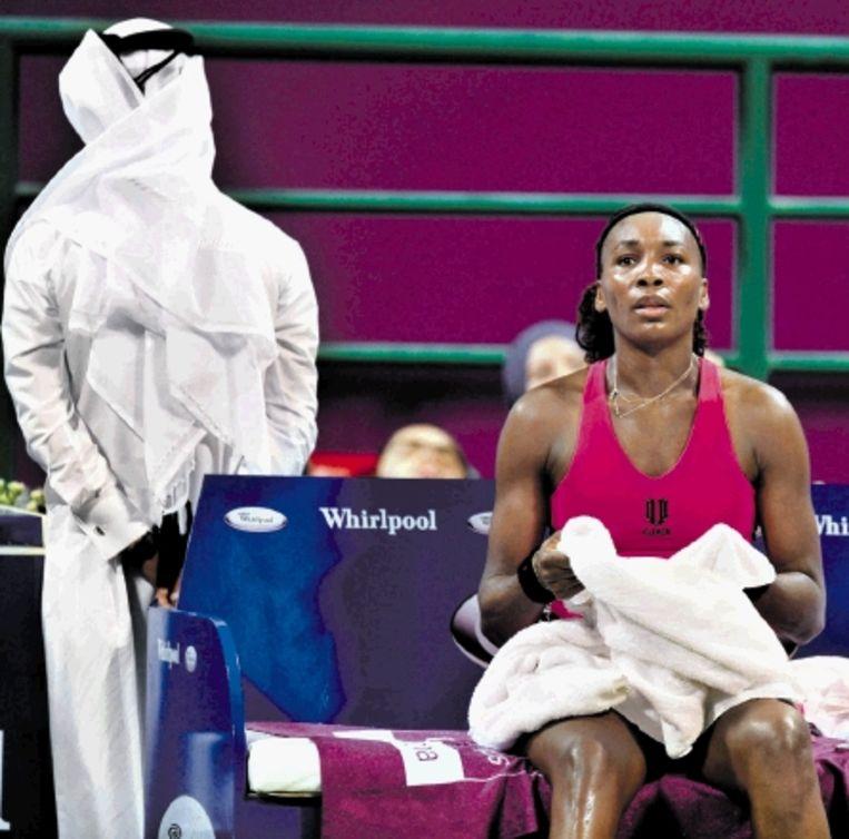Venus Williams grijpt naar de handdoek in een pauze van de partij tegen Dementjeva, terwijl een veiligheidsofficial zijn blik richt naar de tribunes van het Khalifa Stadium in Doha. Williams verloor de wedstrijd en moet vandaag van haar zuster Serena winnen om uitzicht te houden op een plaats in de halve finales. ( FOTO EPA) Beeld