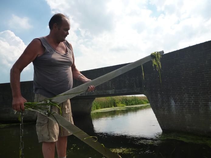 Albert van de Geer showt de vlijmscherpe onderwatermessen van zijn maaiboot.