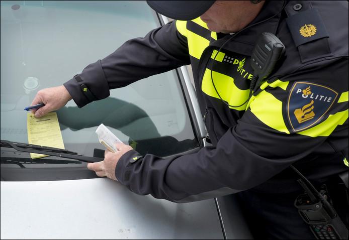 Een agent legt een bon onder de ruitenwisser van een foutparkeerder.