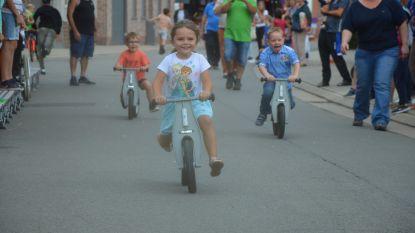 Kinderen koersen op driewielers, loopfietsjes en trottinetten tijdens kermis Voorde