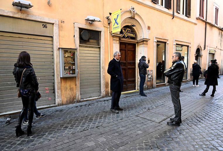 Mensen in Rome houden afstand van elkaar terwijl ze wachten voor de afhaalpizzeria. Beeld AFP