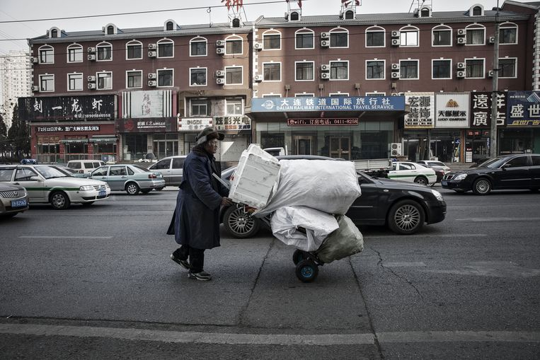 Een man verzamelt afval in de noordoostelijke stad Dalian. De teruggang van de industrie heeft veel mensen werkloos gemaakt. Beeld Bloomberg via Getty Images