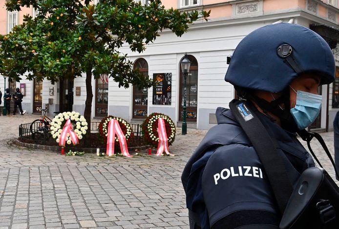 Een politieman waakt bij de plek waar kransen zijn gelegd voor de slachtoffers van moslimterrorist Kujtim Fejzulai.