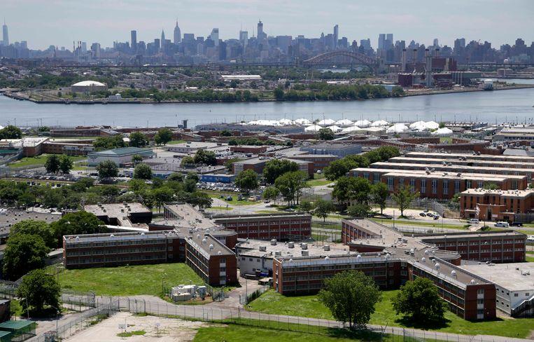 Het gevangeniscomplex van Rikers Island op de voorgrond, aan de overkant de skyline van Manhattan.