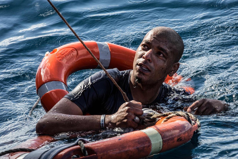 Een Libische migrant wordt uit het ijskoude water van de Middellandse Zee gevist door medewerkers van de Duitse hulporganisatie Sea-Watch. De man was vrijdag vanaf het onder Nederlandse vlag varende schip Sea-Watch 3 in het water gesprongen, in een poging zwemmend de kust van Malta te bereiken. Beeld AFP