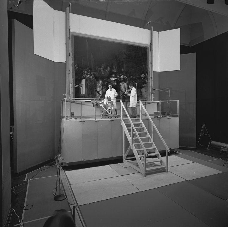 Schilderijenrestauratoren Roy Hesterman en Luitsen Kuiper tijdens de behandeling van de Nachtwacht in 1975-76. Beeld Rijksmuseum
