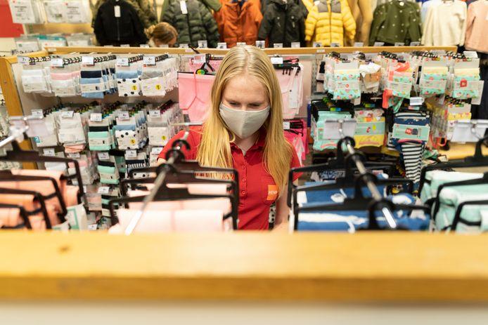 Hema-medewerkster Marit vult de babykleding bij in de binnenstad van Zutphen. Al het personeel van de vestiging moet verplicht een mondkapje voor.