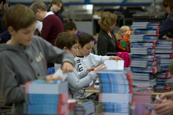 Kinderen en vrijwilligers stickeren zwerfboeken die later uitgereikt kunnen worden. Foto ter illustratie.