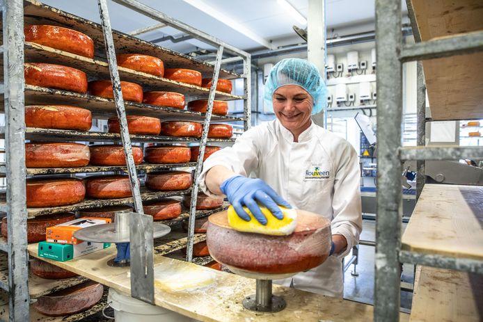 Een medewerkster legt de laatste hand aan de kaas. Onder leiding van directeur Klaas Hokse zijn 341 verschillende soorten kazen gemaakt.