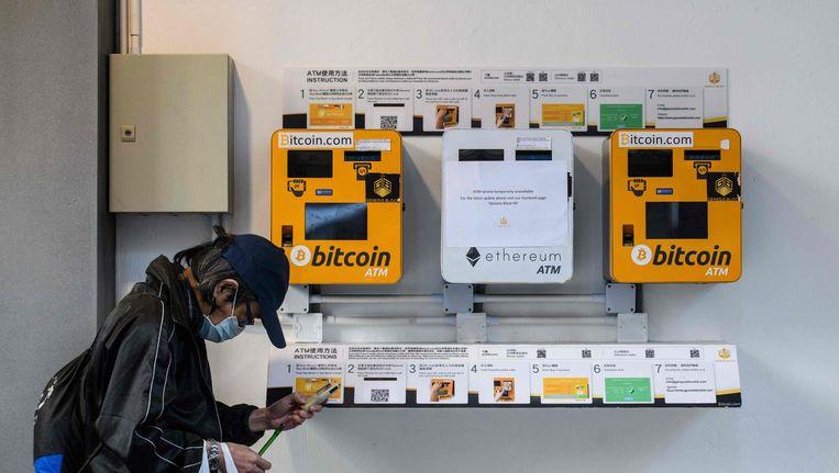 Een Chinese man gebruikt zijn telefoon terwijl hij langs een automaat voor bitcoins loopt. Beeld afp