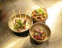 Drie typisch Pintx-gerechten: carpaccio on a stick, sweet potato fries en rundertataki.