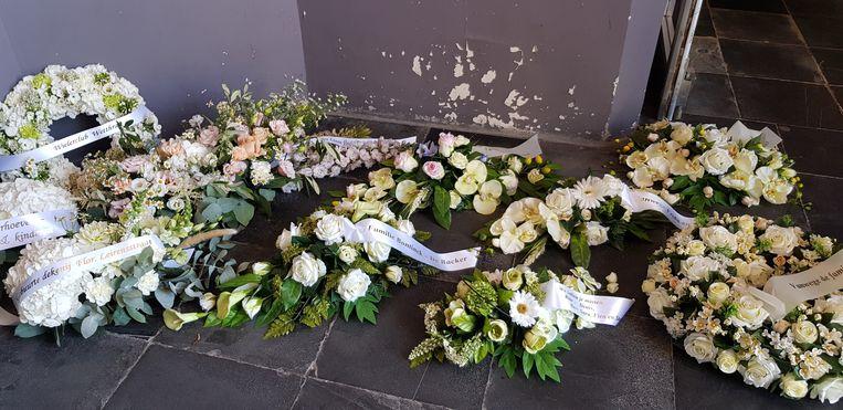 UItvaart Michiel remory : een massa bloemen in het portaal van de kerk.