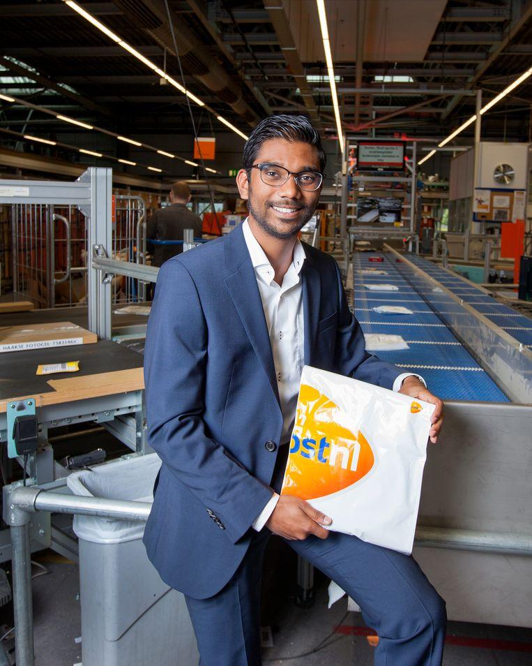 Nikesh Jalgal bij de SMO (Sorteer Machine Overige) van PostNL. In zijn hand de envelop die je thuis eenvoudig vacuum kunt drukken, zodat ook kledingstukken door de brievenbus kunnen. Beeld Maartje Geels