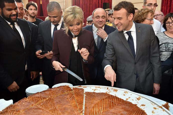 De Franse president Emmanuel Macron en zijn vrouw Brigitte hebben, tijdens een feestelijke ceremonie in het Élysée-paleis in Parijs, een traditionele 'Driekoningentaart' in stukken gesneden om uit te delen aan alle aanwezigen. Foto Christophe Archambault