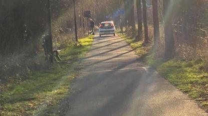 Oudere dame rijdt met auto op oude spoorwegbedding voor fietsers
