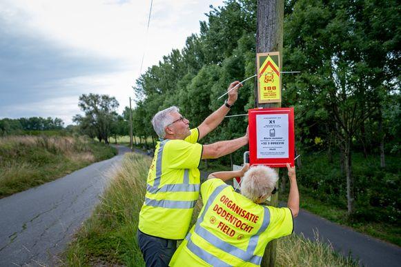 Dodentocht-medewerkers brengen bewegwijzering aan op het parcours van de Dodentocht in Buitenland (Bornem)