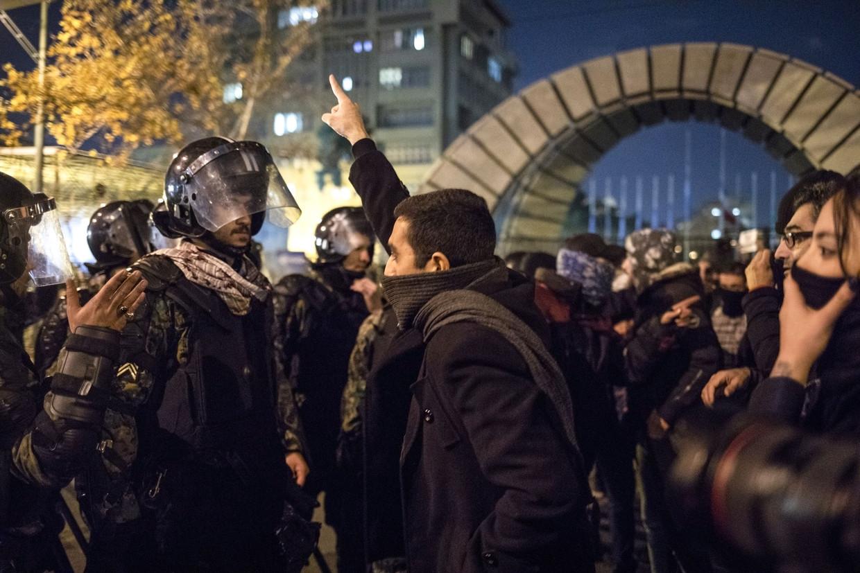 Een Iraanse man staat tegenover een politeman tijdens protesten bij de Amir Kabir Universiteit in Teheran.