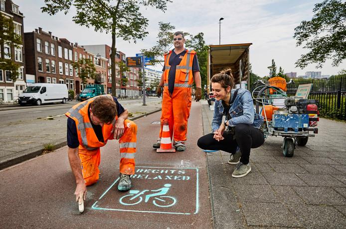 Tessa Leferink kijkt toe hoe de groene wegmarkering op het fietspad wordt aangebracht.