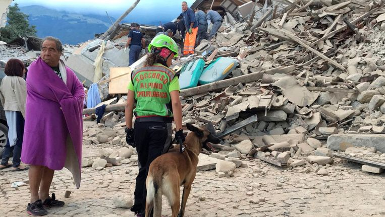 Inwoners van Amatrice bekijken de schade na de aardbeving in het midden van Italië. Beeld reuters