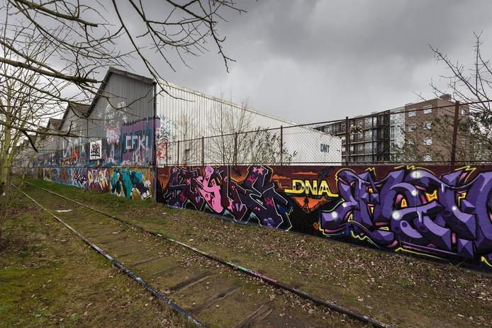 De gedoogwand met het kenmerkende verlaten spoorlijntje moet wijken voor huizen.