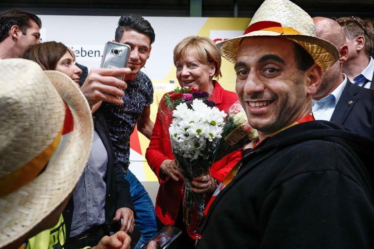 Angela Merkel poseert met een vluchteling die naar Duitsland kwam na haar toespraak in 2015. Dit soort foto's zijn een doorn in het oog van extreem-rechtse betogers. Beeld null