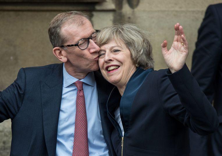 Theresa May krijgt een kus van haar man Philip John May. Beeld AFP