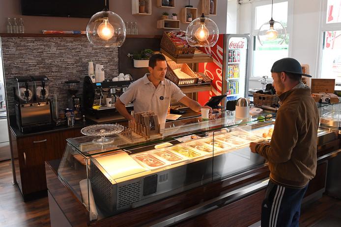 De Cuijkse ondernemer Michiel Aalders helpt een klant in het opgeknapte stationsgebouw van Cuijk.