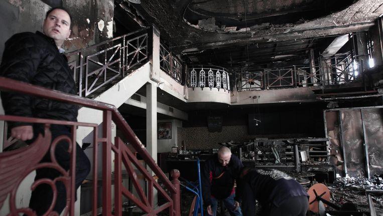 Schoonmakers aan het werk in een uitgebrand café in het centrum van Athene. Beeld AP