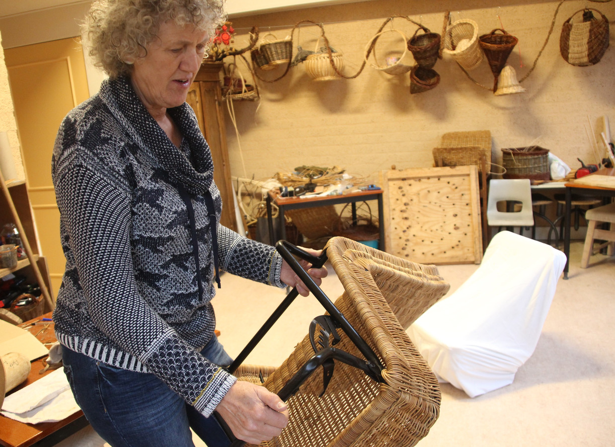 Mandaniet, vlechtster Anita van Kraaij uit Veghel, laat de lastig bereikbare plekjes zien aan de onderkant van de rotan stoel van de DAF-kini.