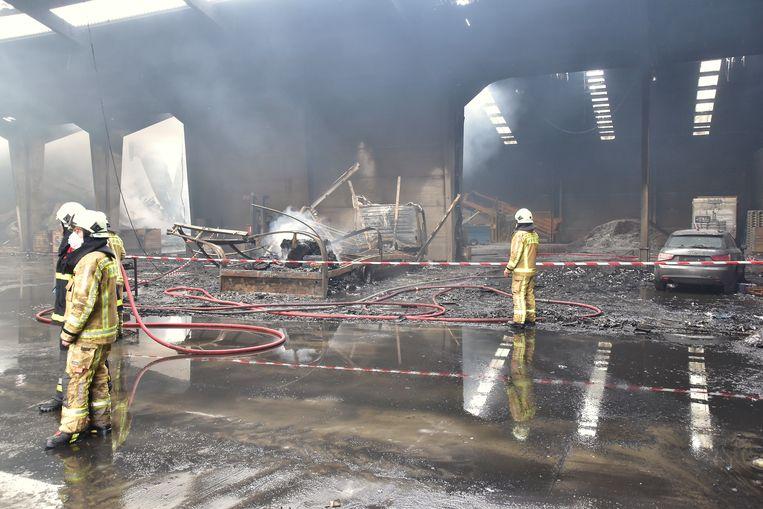 De brand ontstond waarschijnlijk door kortsluiting aan een vrachtwagen (centraal op de foto) die in de grote loods geparkeerd stond. Ook een Audi raakte beschadigd door de brand.