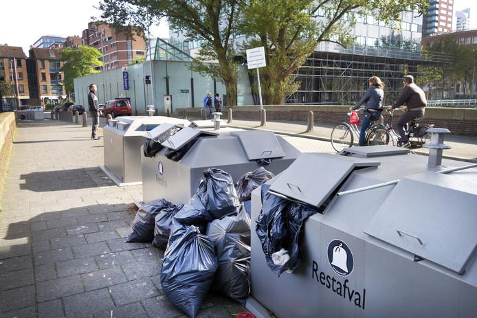 Foto ter illustratie. 'Pleegouders' van een vuilcontainer houden het rond de bakken schoon.