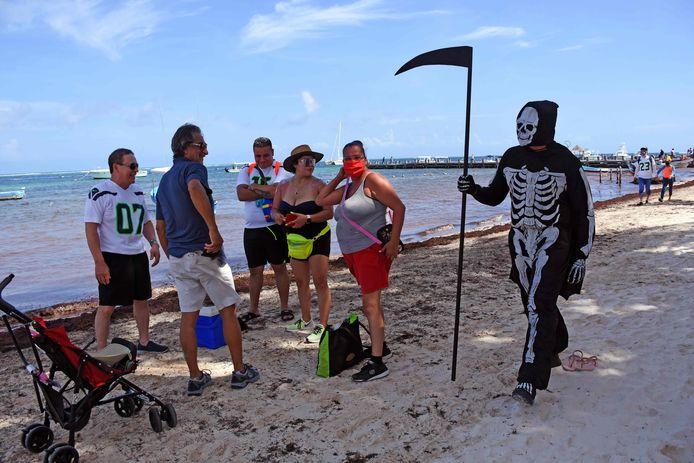Een man verkleed als 'de dood' waarschuwt toeristen in Puerto Morelos naaer huis te gaan, omdat de stranden gesloten zijn