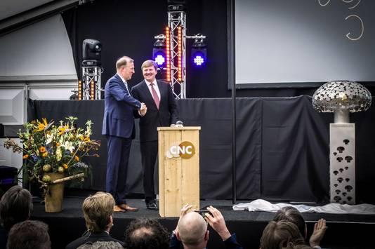 Koning Willem-Alexander schudt directeur Tom van Wijk van CNC de hand na de onthulling van het kunstwerk van Anita en Kees Lintzen.
