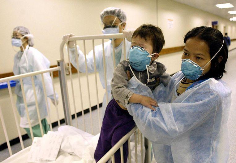 Een jongetje in een ziekenhuis in Hong Kong tijdens de SARS-epidemie in 2003 Beeld afp