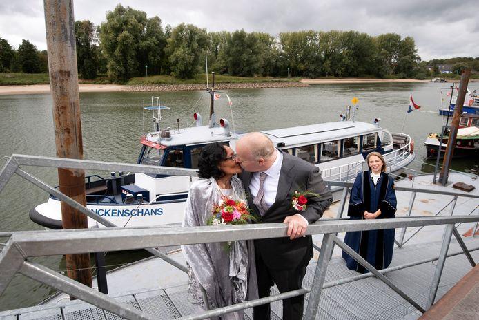 Gert van Wijk en Margriet Martowidjojo geven elkaar nog snel een kus voordat ze aan boord gaan van de Schenckenschans. Daar zal trouwambtenaar Charlotte Waardenburg (rechts) hen even later in de echt verbinden.